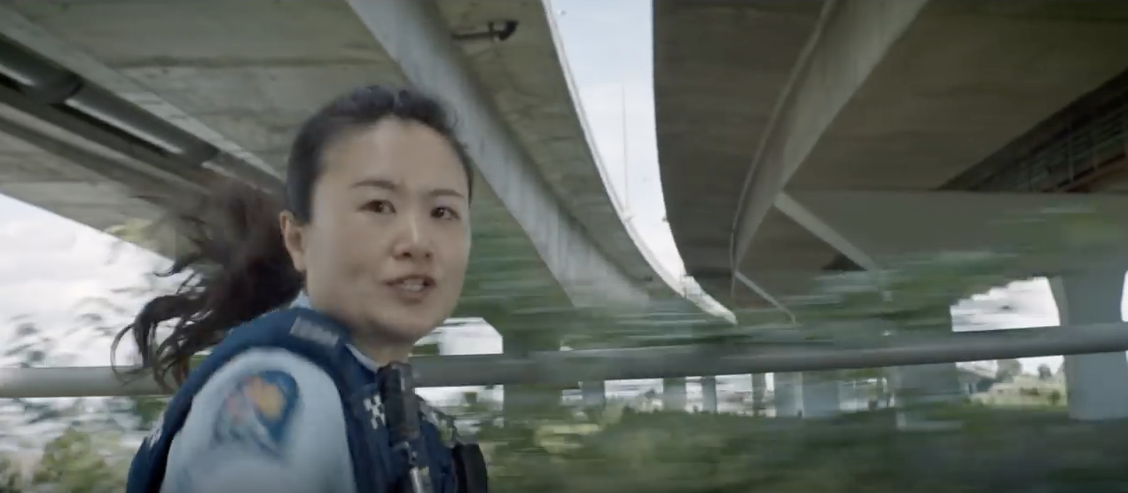 Image of woman police officer, filmed from a side profile, running-left-to-right across the screen in hot pursuit