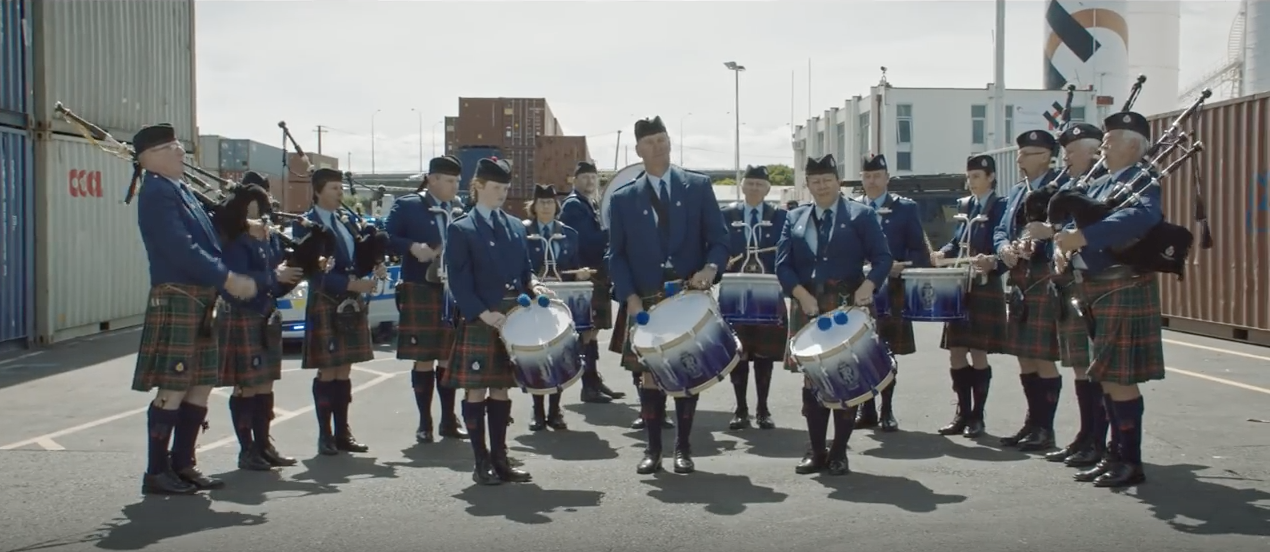 Image of men in kilts playing bagpipes and playing drums, distracting the female officer and her police team
