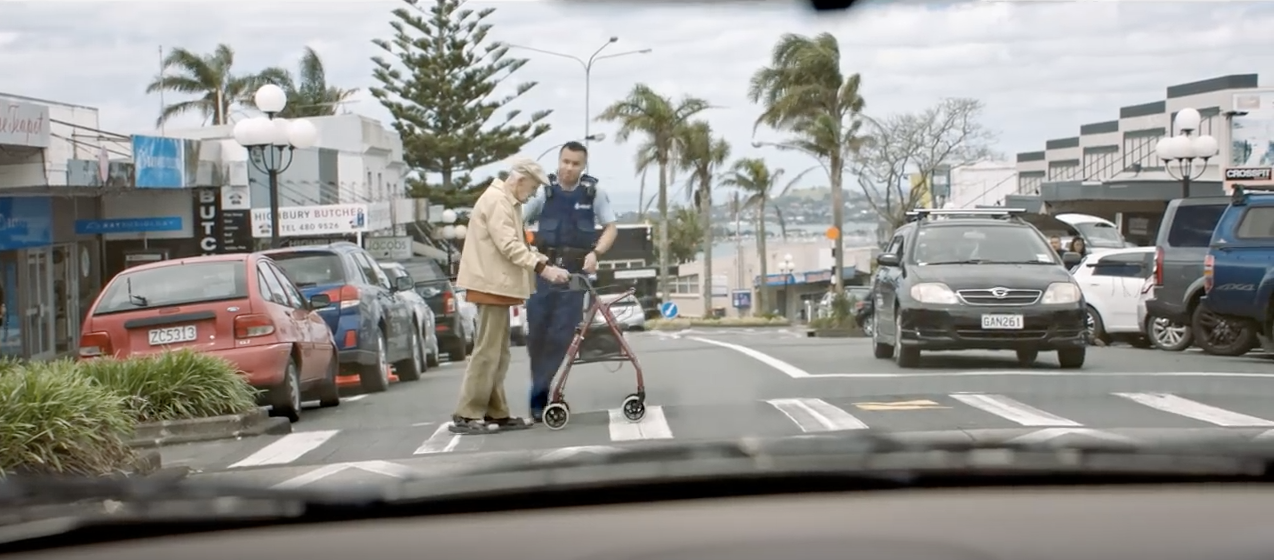 Image of male police officer helping an elderly man with his walker cross the street safely