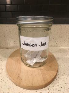 Image of the Jargon Jar with pieces of paper inside that contain jargon phrases, and will include circle back after this post is done