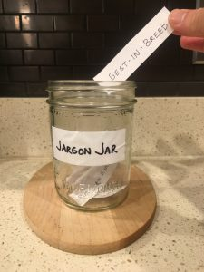 Image of hand depositing paper that says best-in-breed into the open Jargon Jar