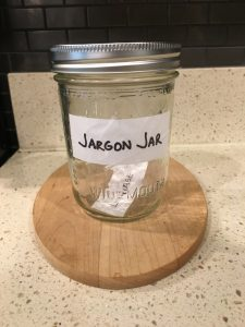 Image of sealed Jargon Jar with the hand-written 'Leverage' paper inside it