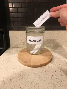 Image of a hand placing a handwritten 'Push the envelope' note into the Jargon Jar