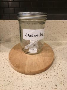 Image of sealed Jargon Jar, containing a paper with 'leverage' and a paper with 'push the envelope' sealed inside
