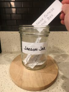 Image of hand depositing a piece of paper that reads think outside the box into the open Jargon Jar