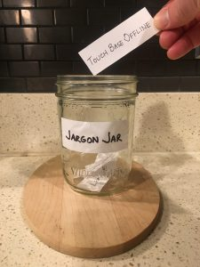 Image of a hand placing a handwritten Touch base offline note into the Jargon Jar