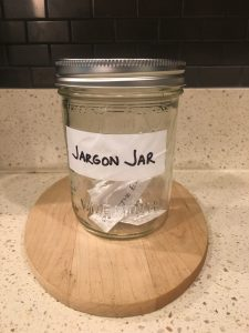 Image of the Jargon Jar with pieces of paper inside that read leverage, push the envelope, and touch base offline